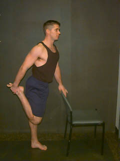 man-showing-standing-quad-stretch-holding-chair.jpg